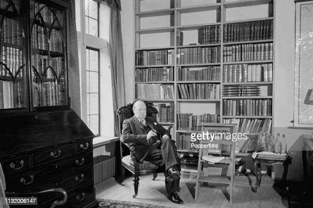 British politician Winston Churchill pictured seated with a cigar in the library of Chartwell country house near Westerham in Kent England in October...