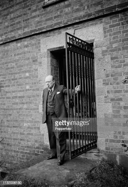 British politician Winston Churchill pictured standing beside a iron gate in the grounds of Chartwell country house near Westerham in Kent England in...