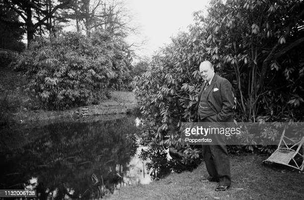 British politician Winston Churchill pictured standing beside a pond in the grounds of Chartwell country house near Westerham in Kent, England in...
