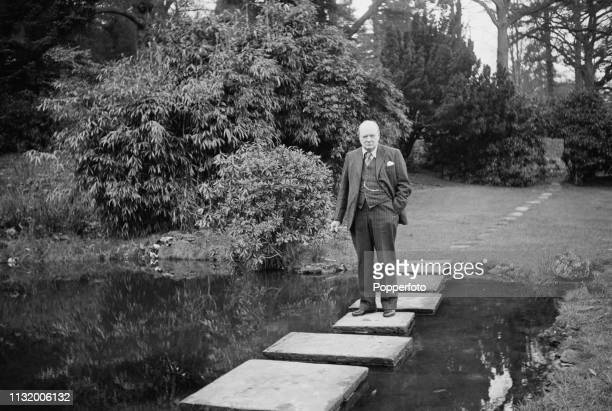 British politician Winston Churchill pictured standing on stepping stones over a pond in the grounds of Chartwell country house near Westerham in...