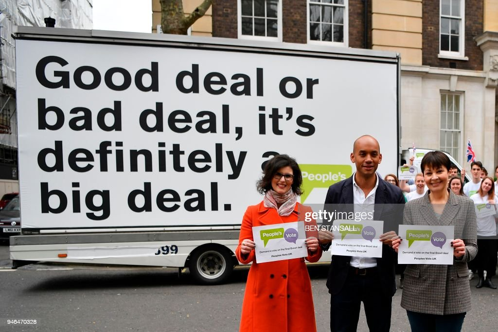 British politicians, Labour Party MP Chuka Umunna (C), Liberal Democrat MP Layla Moran (L) and Green MP Caroline Lucas (R) pose in front of an advertising board to launch the Peoples Vote advertising campaign in central London on April 15, 2018 calling for a referendum on the final Brexit deal. A new cross-party campaign for a referendum on Britain's EU departure deal launched on April 15, insisting the British public -- and not just politicians -- should be given a say. / AFP PHOTO / Ben STANSALL