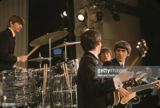 British pop and rock music group the Beatles talk together on stage just before their performance on 'The Ed Sullivan Show' New York New York...