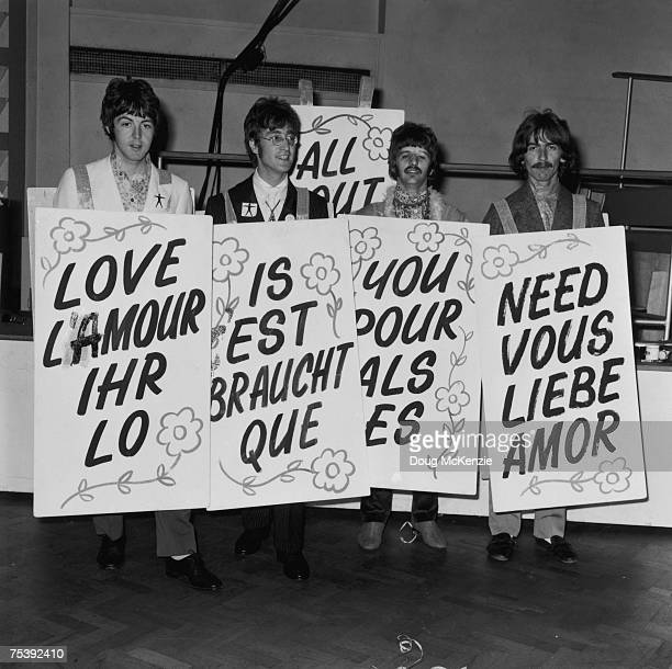 British pop group The Beatles at EMI studios holding placards proclaiming 'All You Need Is Love' in four languages in preparation for a global...