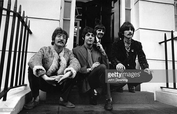 British pop group The Beatles from left to right John Lennon Paul McCartney Ringo Starr and George Harrison sitting on the steps outside their...