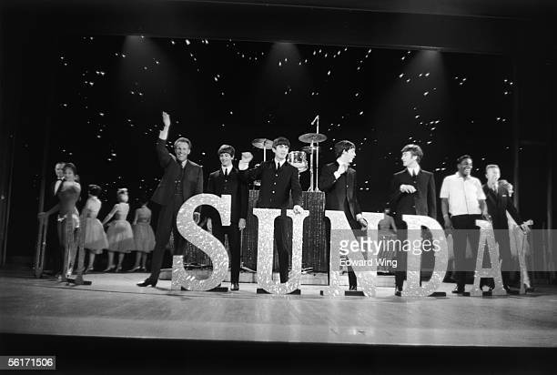 British pop group The Beatles on stage with TV presenter Bruce Forsyth at the London Palladium, 3rd October 1963. From left to right, Bruce, Ringo,...