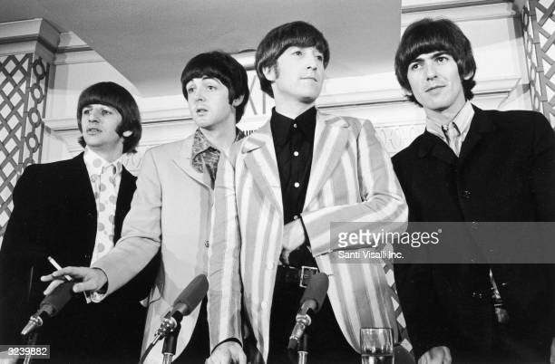 British pop group the Beatles standing in front of four microphones at a press conference where they discussed their concert at Shea Stadium, New...