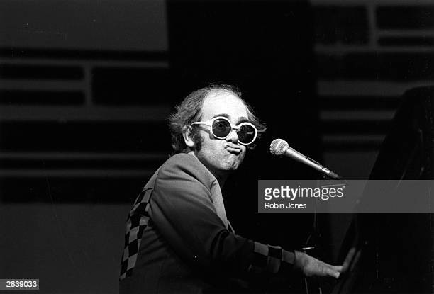 British pop singer and pianist Elton John pulls a face while playing the piano during a concert at the Rainbow Theatre London
