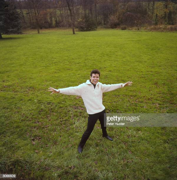 British pop singer Cliff Richard born Harry Webb standing in the garden of his home