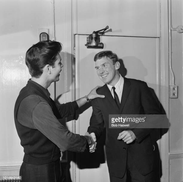 British pop singer Cliff Richard shaking hands with with Shadows bassist, Brian 'Licorice' Locking, 4th November 1963.