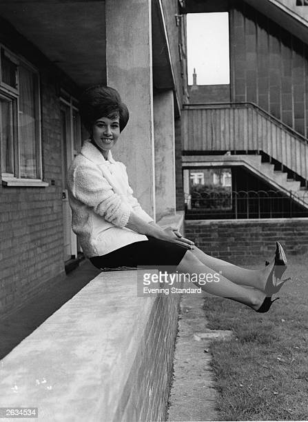 British pop singer Helen Shapiro pictured swinging her legs outside her home on the Parkside Estate Victoria Park Road London Original Publication...