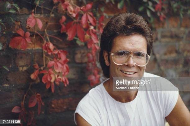 British pop singer musician and actor Cliff Richard pictured wearing a pair of clear oversized glasses at a press conference in 1984