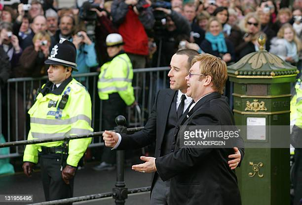 British pop singer Sir Elton John and his partner David Furnish pose for photographs at the Guildhall in Windsor 21 December 2005 after conducting a...