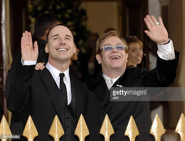 British pop singer Sir Elton John with his partner David Furnish wave to fans and media at the Guildhall in Windsor 21 December 2005 after conducting...