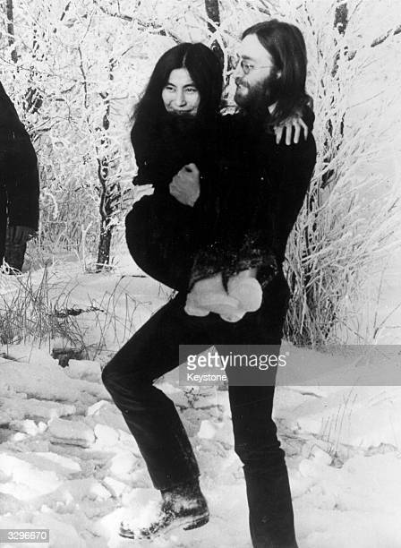 British pop singer songwriter and guitarist John Lennon carries his wife artist Yoko Ono across the snow in North Jutland Denmark where they are...