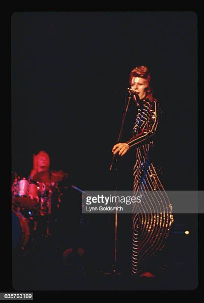 1970 British pop star David Bowie in a wild costume during a concert performance He wears a black suit with thin white stripes and exaggeratedly...