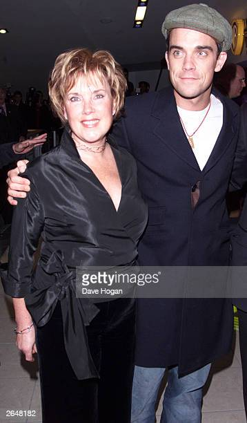 British pop star Robbie Williams and his mother arrive at the premiere of the film Nobody Someday at Warner Brothers Cinema Sheperds Bush on December...