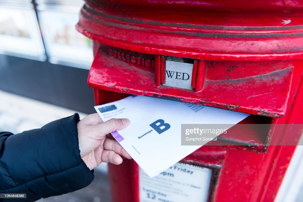 British Postal voting envelop is being dropping into a postbox : Stock Photo