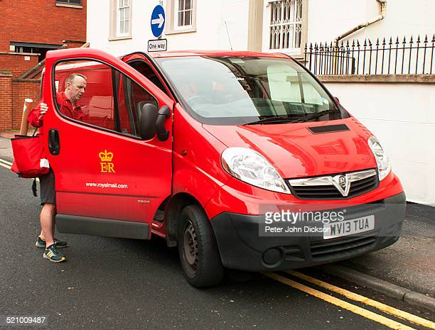 A British postal worker is preparing to go on delivery On foot leaving his van parked on the street in Nottingham UK