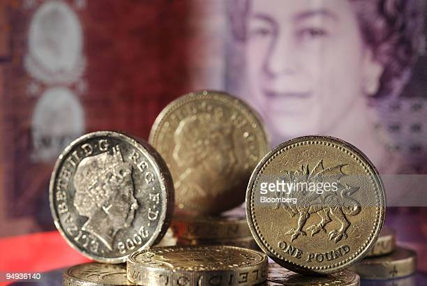 British pound coins sit against a backdrop of a twenty pound note arranged for a photograph in Cambridge, U.K., on Monday, Jan. 26, 2009. The pound...