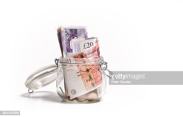 british pound notes in savings jar - british pound sterling note stock pictures, royalty-free photos & images