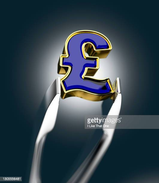 a british pound sterling sign held carefully within tweezers - atomic imagery stock pictures, royalty-free photos & images