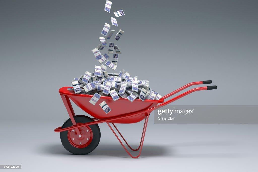 British pounds falling into red wheelbarrow : Stock Photo