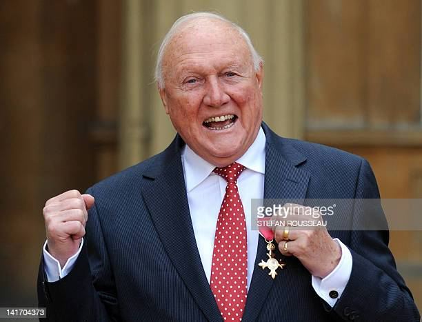 British presenter Stuart Hall poses with his Officer of the British Empire medal presented to him by Britain's Queen Elizabeth II at an investiture...