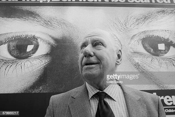 British press photographer Bert Hardy stands in front of a poster for the Church of England Children's Society, 17th February 1984. He is best known...