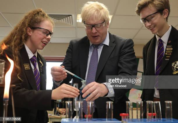 British Prime Minister and Conservative Party leader, Boris Johnson helps Year-11 Head Girl Ruby Culter and Head Boy Matthew Upright with a science...