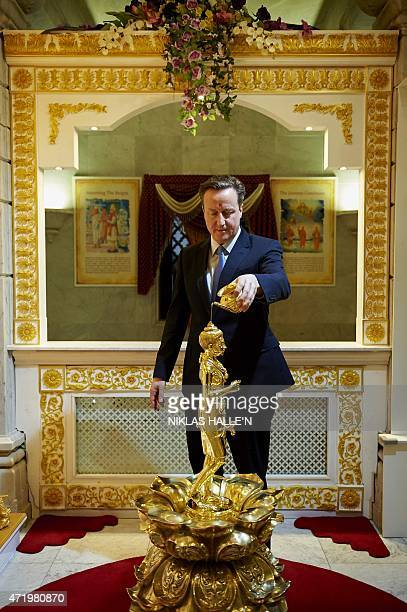 British Prime Minister and Conservative Party Leader David Cameron is pictured as he participates in a Abhishek ceremony during a visit to the...