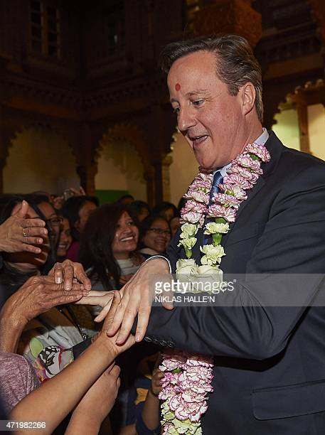 British Prime Minister and Conservative Party Leader David Cameron is pictured as he greets worshippers during a visit to the Neasden Hindu Temple in...