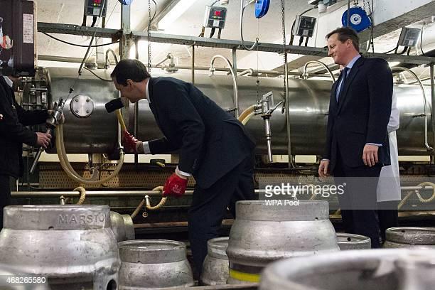 British Prime Minister and Conservative party leader David Cameron looks on as British Finance Minister George Osborne hammers a sealing stopper into...