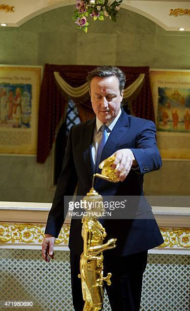 British Prime Minister and Conservative Party Leader David Cameron participates in a Abhishek ceremony as he visits the Neasden Hindu Temple in...