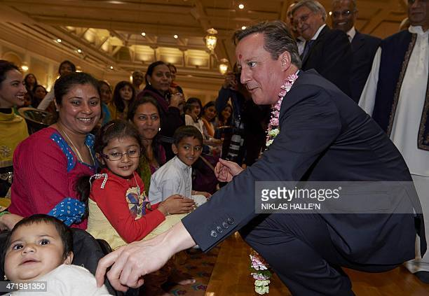 British Prime Minister and Conservative Party Leader David Cameron greets worshippers during a visit to the Neasden Hindu Temple in London on May 2...