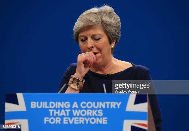British Prime Minister and leader of the Conservative Party Theresa May MP stops to cough as she loses her voice during her keynote speech on the...