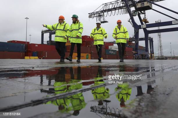 British Prime Minister Boris Johnson and Chancellor of the Exchequer Rishi Sunak , are reflectd in a puddle as they walk past shipping containers on...
