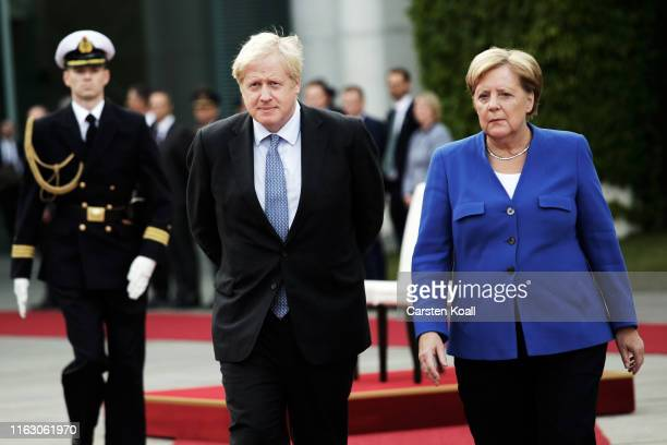 British Prime Minister Boris Johnson and German Chancellor Angela Merkel attend a guard of honor upon Johnson's arrival at the Chancellery on August...