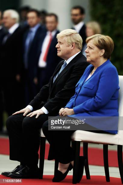 British Prime Minister Boris Johnson and German Chancellor Angela Merkel leave a press conference at the Chancellery on August 21 2019 in Berlin...