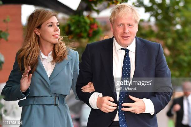 British Prime Minister Boris Johnson and his girlfriend Carrie Symonds arrive at the Conservative Party Conference on September 28 2019 in Manchester...