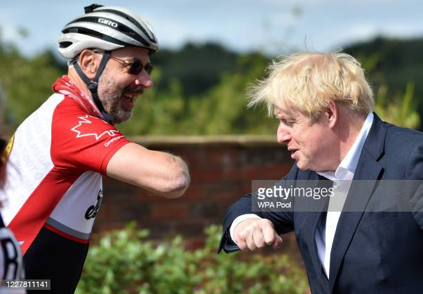 British Prime Minister Boris Johnson bumps elbows with cyclist Robert Cleave at the Canal Side Heritage Centre in Beeston on July 28 2020 in Beeston...