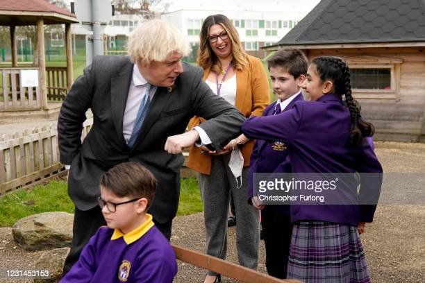 British Prime Minister Boris Johnson bumps elbows with with Head Girl Hirah Hussain during a visit to St Mary's CE Primary School on March 1, 2021 in...