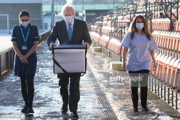 British Prime Minister Boris Johnson carries doses of the Oxford/AstraZeneca coronavirus vaccine for mobile distribution at Barnet FC's ground, The...