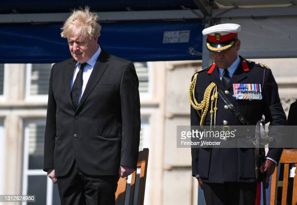 British Prime Minister Boris Johnson during the one minute silence for Prince Philip, as he attends Passing-out parade at Britannia Royal Naval...