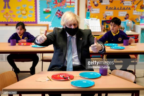 British Prime Minister Boris Johnson gives a thumbs up as he joins a Year 2 maths lesson during a visit to St Mary's CE Primary School on March 1,...