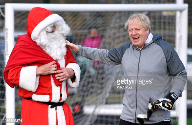 British Prime Minister Boris Johnson greets a man dressed as Father Christmas during the warm up before a girls' soccer match between Hazel Grove...