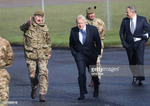 British Prime Minister Boris Johnson greets troops with Secretary of State for Northern Ireland Brandon Lewis and Brigadier Chris Davies, Commander...
