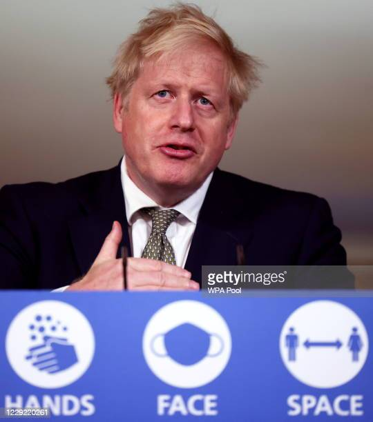 British Prime Minister Boris Johnson has a sip of water during a news conference on the coronavirus at 10 Downing Street on October 22 2020 in London...