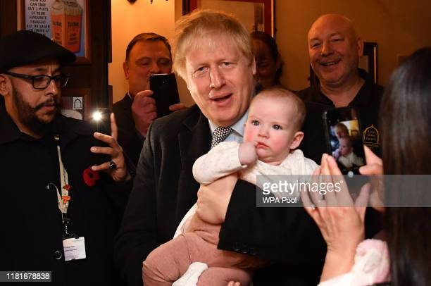 British Prime Minister Boris Johnson holds a baby as he meets supporters as he campaigns ahead of the general election at the Lynch Gate Tavern on...