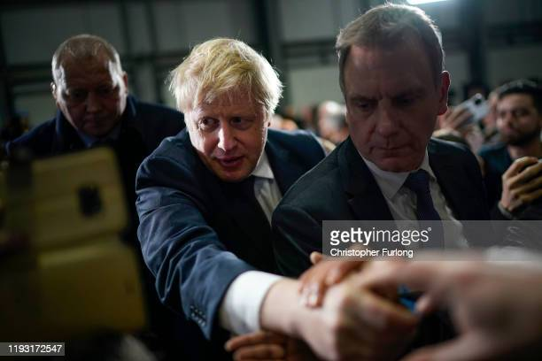 British Prime Minister Boris Johnson is applauded by supporters after speaking at the Globus Group factory on December 10, 2019 in Manchester,...