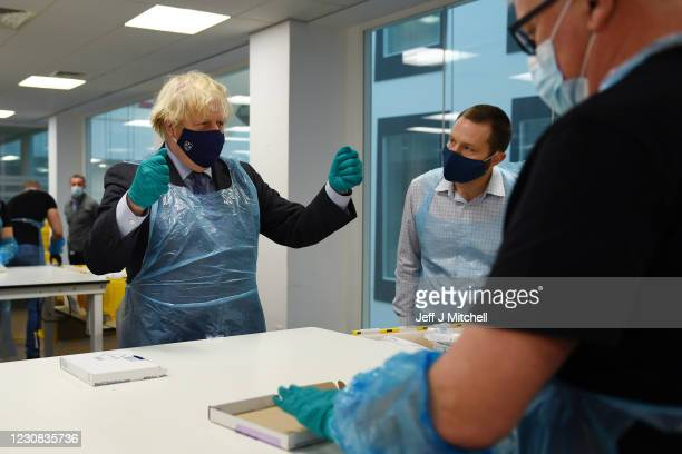 British Prime Minister Boris Johnson is shown the Lighthouse Laboratory used for processing PCR samples, during a visit to the Queen Elizabeth...